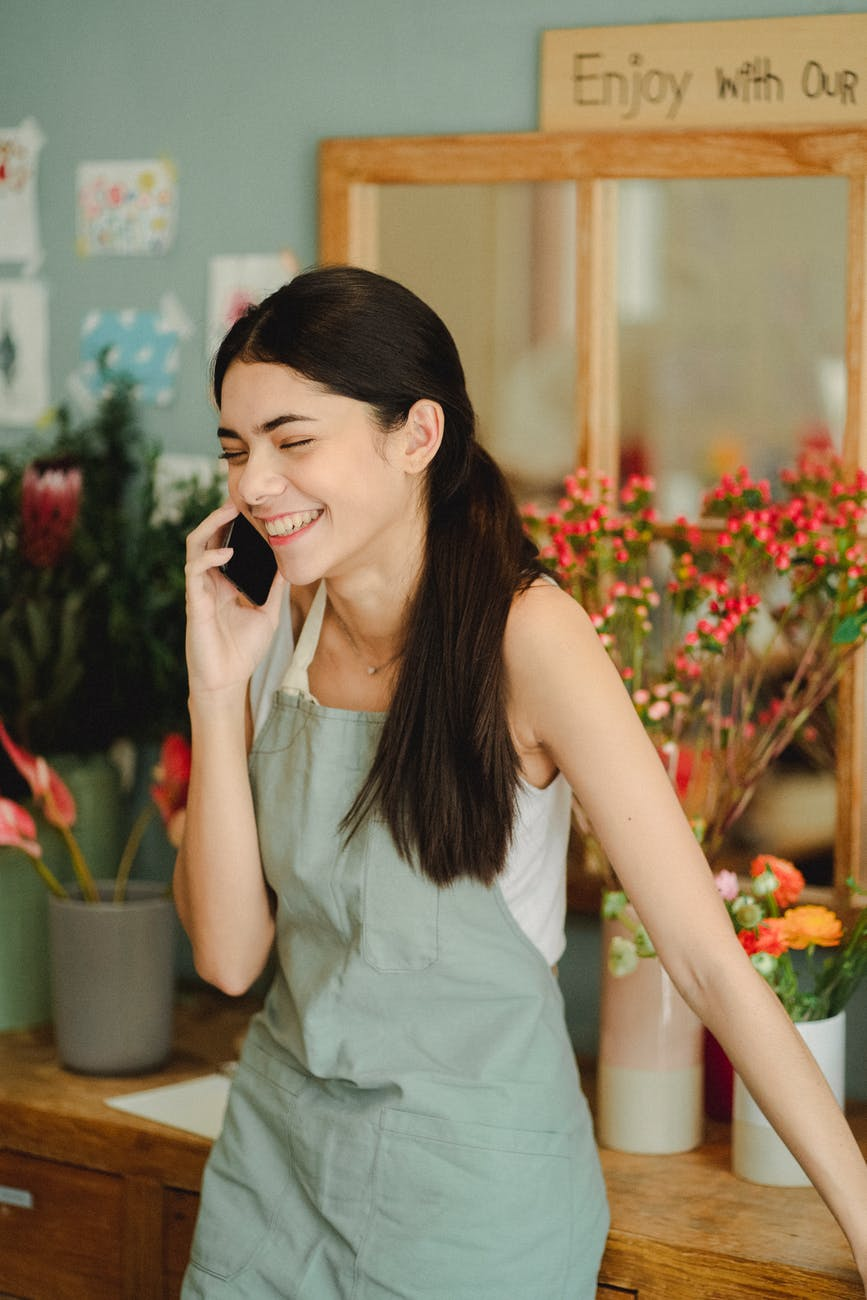 smiling woman speaking on phone in floral store